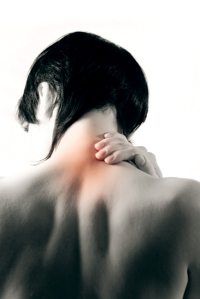 Woman holds a hand on pain neck. Isolated on white background